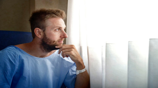 young-injured-man-in-hospital-room-sitting-alone-in-pain-looking-on-window